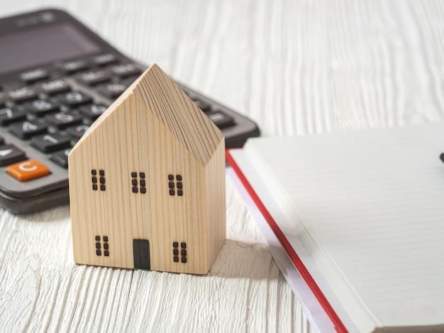 Blokhuismodel, rekenmachine en boek op witte houten achtergrond. hypotheekplan voor de woningsector en belastingbesparingsstrategie voor woningen