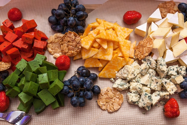 Blokjes roodgroene kaas met fruit op tafel