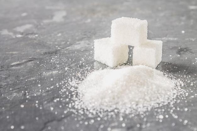 Blokjes suiker en suikerzand op een donkergrijze achtergrond.