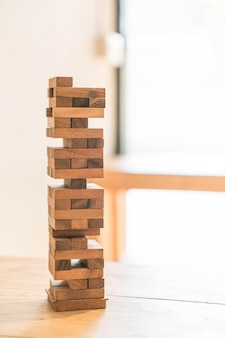 Blokkeert houtspel (jenga) op houten tafel