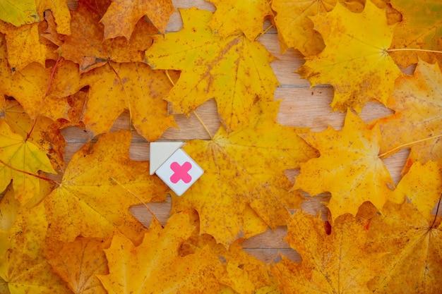 Blokken met medisch rood kruis naast bladeren op een houten tafel