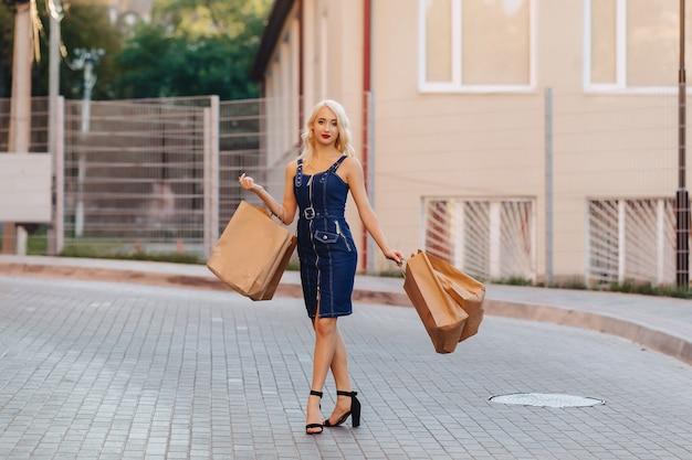 Blond aantrekkelijk meisje in een hoed na het winkelen in de stralen van de de zomerzon