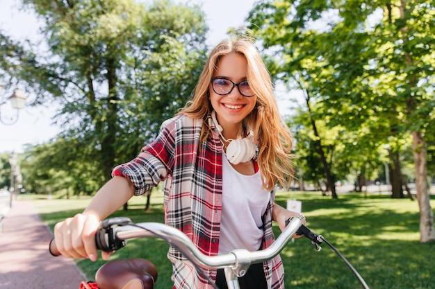 Blond blij meisje dat rond park in ochtend berijdt. buitenfoto van betoverende jonge dame met fiets die positieve emoties uitdrukt.