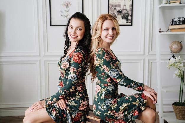 Blond en brunette in korte groene jurken met patronen. twee mooie meisjes in een witte studio.