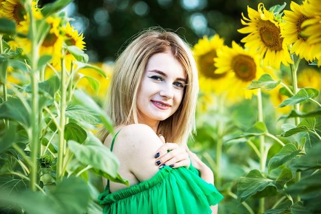 Blond europees meisje in een groene jurk op aard met zonnebloemen