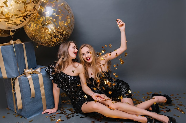 Blond feestvarken grapje met beste vriend, zittend naast haar cadeautjes. indoor portret van schattige dames in zwarte kledij wachten op kerstfeest.