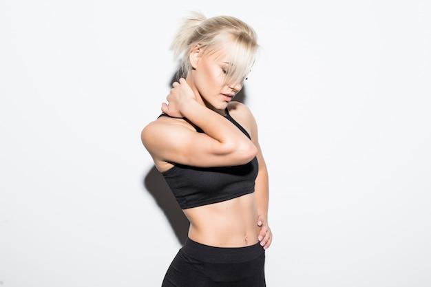 Blond fitness meisje wordt moe en vermoeid voelen in de studio op wit gekleed in zwarte sportkleding