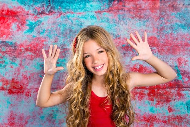 Blond gelukkig kinderenmeisje in rode gelukkige omhoog wapens