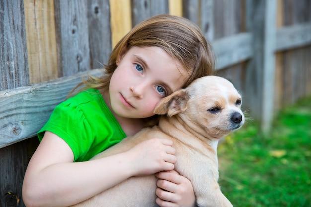 Blond gelukkig meisje met haar chihuahua van een hond portret