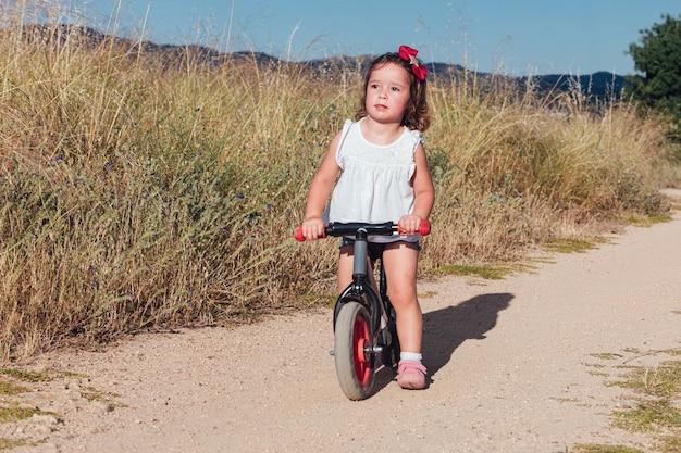 Blond haar meisje fietsen op een onverharde weg