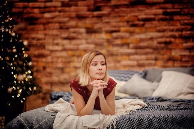 Blond haarmeisje in rode pyjama die op grijs bed ligt dat zijwaarts voor bruine bakstenen muur en kerstboom met lichten van slinger kijkt