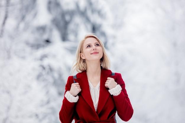 Blond in een rode jas in een besneeuwd bos