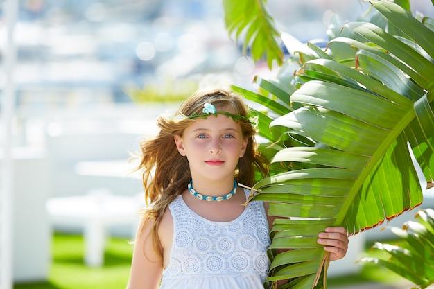 Blond jong geitjemeisje bij de bladeren van de banaanboom in heldere dag