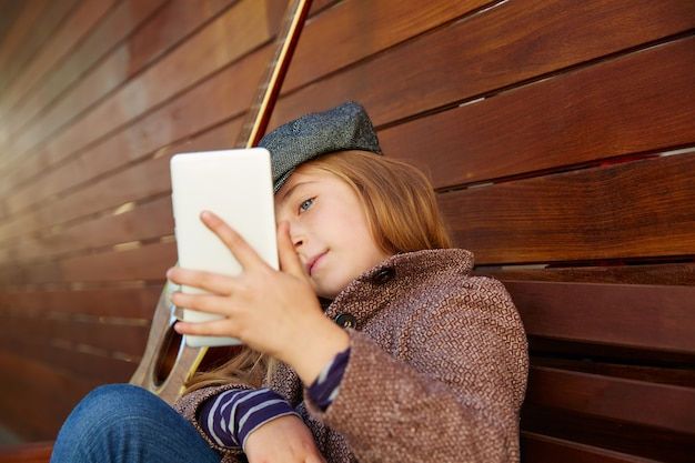 Blond jong geitjemeisje die selfie gitaar en de winterbaret nemen