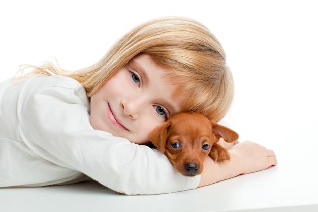 Blond jong geitjemeisje met de minigiftende hond van de pinscherhuisdieren