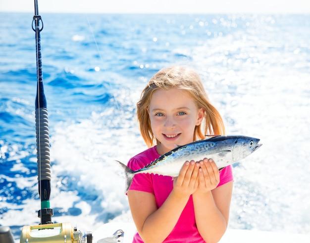 Blond jong geitjemeisje tonijn vissen weinig tonijn gelukkig met vangst