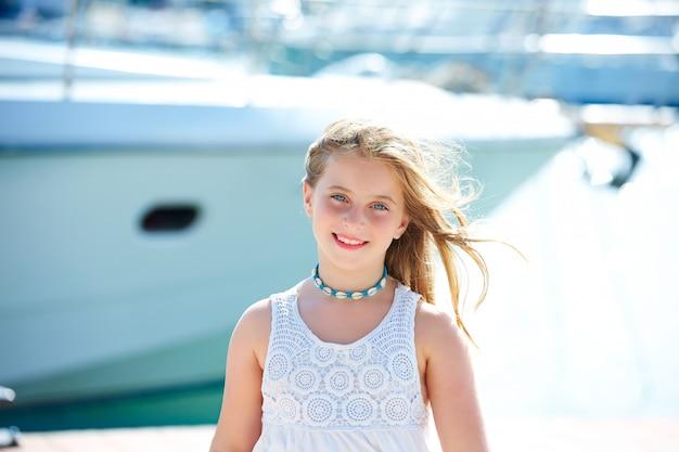 Blond jong geitjetienermeisje in mediterrane haven spanje