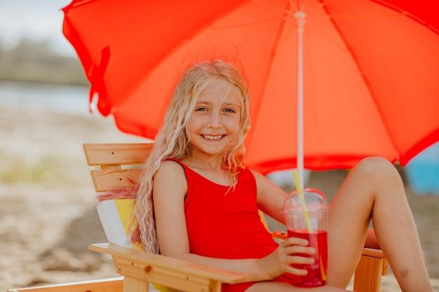 Blond jong meisje in rode zwembroek zittend op een stoel en met een drankje onder rode parasol beach