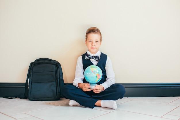 Blond jongetje gekleed in schooluniform zittend op de vloer met een wereldbol en kijkt naar de camera. onderwijs en reisconcept.