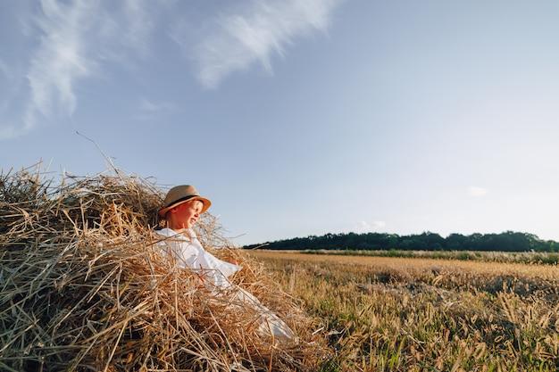 Blond jongetje plezier springen op hooi in veld. zomer, zonnig weer, landbouw. gelukkige jeugd. platteland.