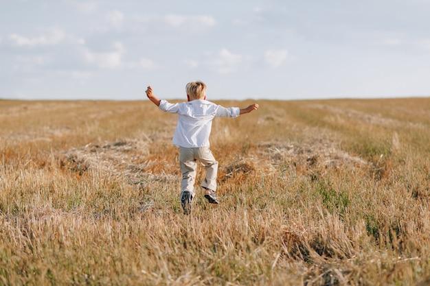Blond jongetje spelen hooi in het veld. zomer, zonnig weer, landbouw.