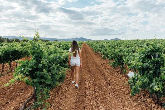 Blond kaukasisch meisje dat naar grote eiken en wijngaardgebieden loopt. landelijke scène.