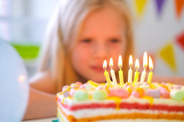 Blond kaukasisch meisje die kaarsen op de cake van de verjaardagsregenboog bekijken, die een wens maken alvorens hen uit op verjaardagspartij blaast. focus op kaarsen. kleurrijke achtergrond met ballonnen