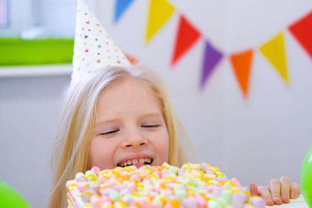 Blond kaukasisch meisje die uit van achter verjaardagstaart gluren met een grappig gezicht op verjaardagspartij. feestelijke kleurrijke achtergrond met ballonnen.