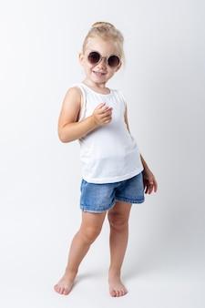 Blond kind in zonnebril poseren op een lichte achtergrond in de studio.