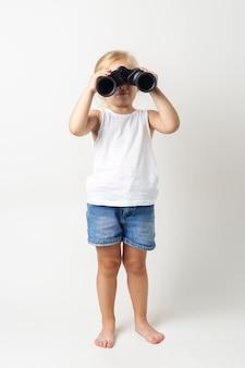 Blond kind kijkt door een verrekijker op een lichte achtergrond in de studio.