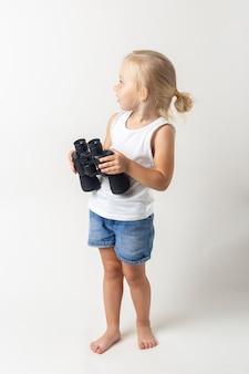 Blond kind met een verrekijker op een lichte achtergrond in de studio.