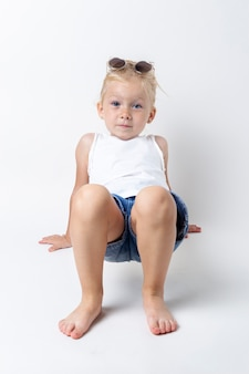 Blond kind met zonnebril poseren op een lichte achtergrond in de studio.