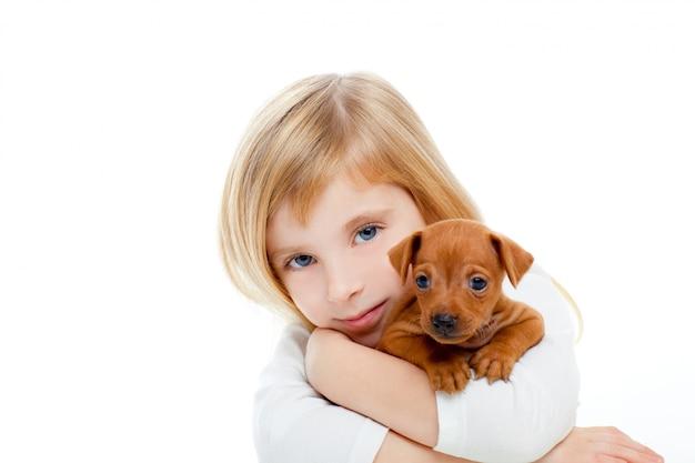 Blond kinderenmeisje met minipinscher van het hondpuppy