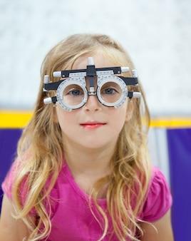 Blond kinderenmeisje met optometrist diopter glazen
