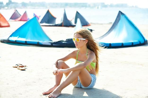 Blond kitesurfen tienermeisje in de zomer strand zitten