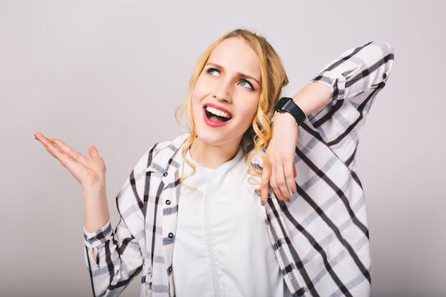 Blond krullend meisje in stijlvolle kleding met ontevreden blik op gezicht luistert gebroken polshorloge. close-upportret van teleurgestelde jonge vrouw met leuk kapsel dat gestreept overhemd draagt, zwaaiende handen