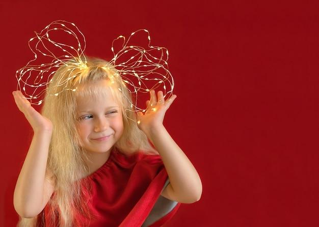 Blond lachend meisje met strik gemaakt van draad kerstverlichting