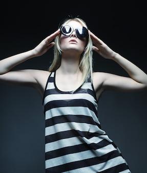 Blond mannequin dragen van een zonnebril poseren in studio