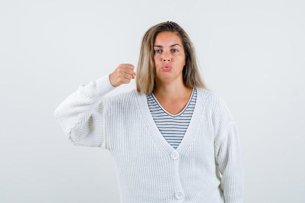 Blond meisje balde vuist, gebogen lippen in gestreept t-shirt, wit vest en jeansbroek en ziet er zelfverzekerd uit. vooraanzicht.