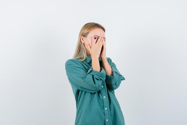 Blond meisje bedekt gezicht met hand en kijkt door vingers in groene blouse en ziet er verlegen uit.