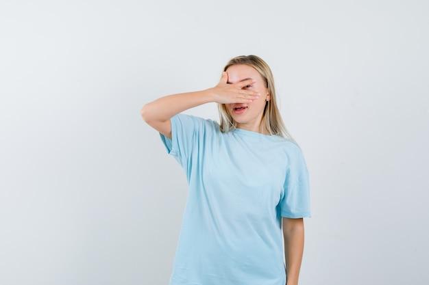 Blond meisje bedekt ogen met hand, kijkt door vingers in blauw t-shirt en kijkt beschaamd, vooraanzicht.