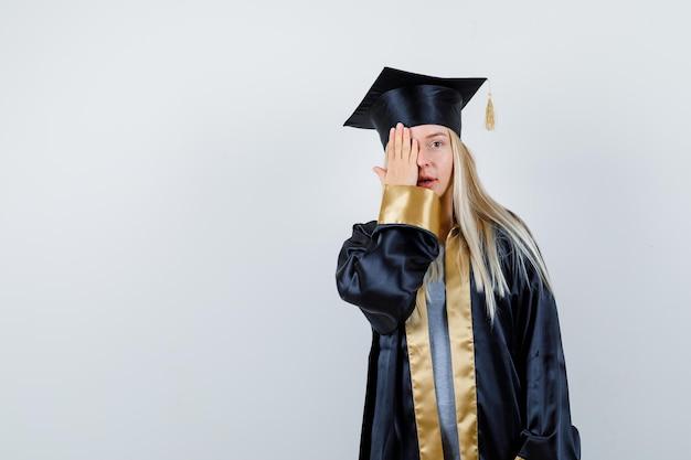 Blond meisje bedekt oog met hand in afstudeerjurk en pet en ziet er serieus uit
