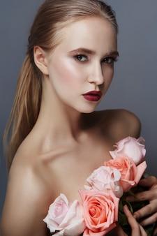 Blond meisje bedrijf steeg met bloemen in de buurt van gezicht. schoonheid