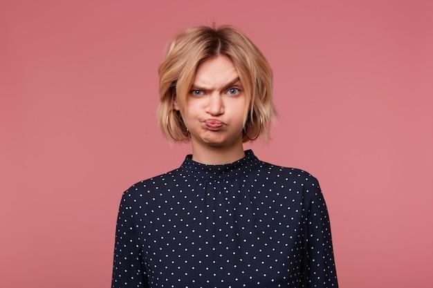 Blond meisje beledigd boos boos, pruilde haar wangen is overweldigd door negatieve emoties, in slecht humeur gekleed in blouse met polka dots, geïsoleerd op roze