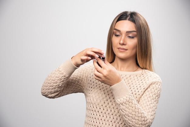 Blond meisje controleert foto's op fotorolletje en voelt zich teleurgesteld.