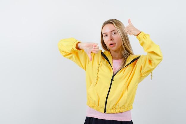 Blond meisje dat duimen op en neer laat zien met beide handen in roze t-shirt en geel jasje en er serieus uitziet