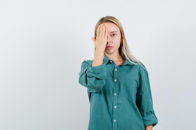 Blond meisje dat een deel van het gezicht bedekt met de hand in een groene blouse en er serieus uitziet.