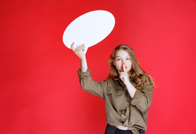 Blond meisje dat een ovale denkbord vasthoudt en om stilte vraagt.