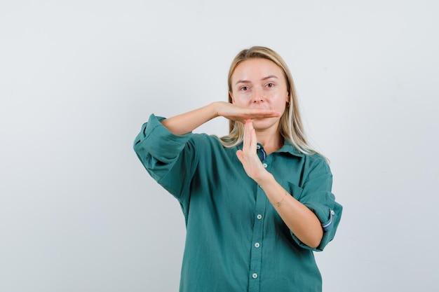 Blond meisje dat een pauzegebaar in een groene blouse toont en er serieus uitziet