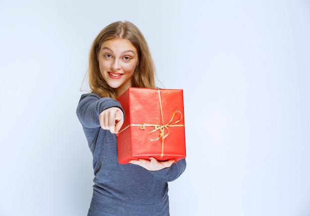 Blond meisje dat een rode geschenkdoos houdt en iemand laat zien.